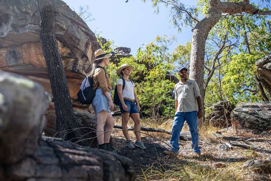 two visitors at Normanby station with an aboriginal traditional owner standing beside sandstone rocks and under gum trees