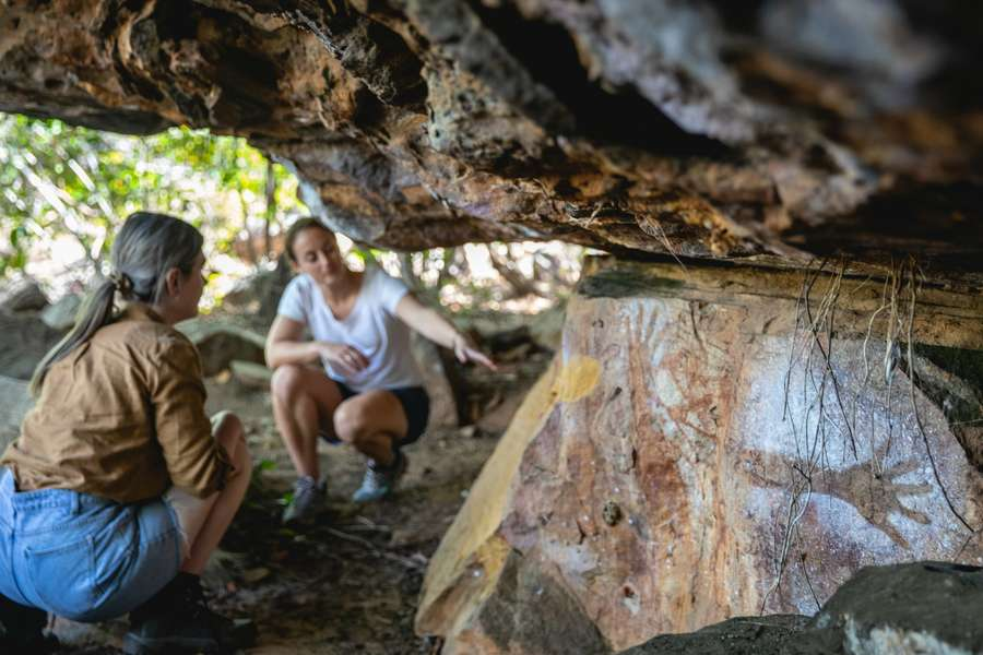 two ladies viewing rock art in a low ceiling rock shelter at Normanby Station