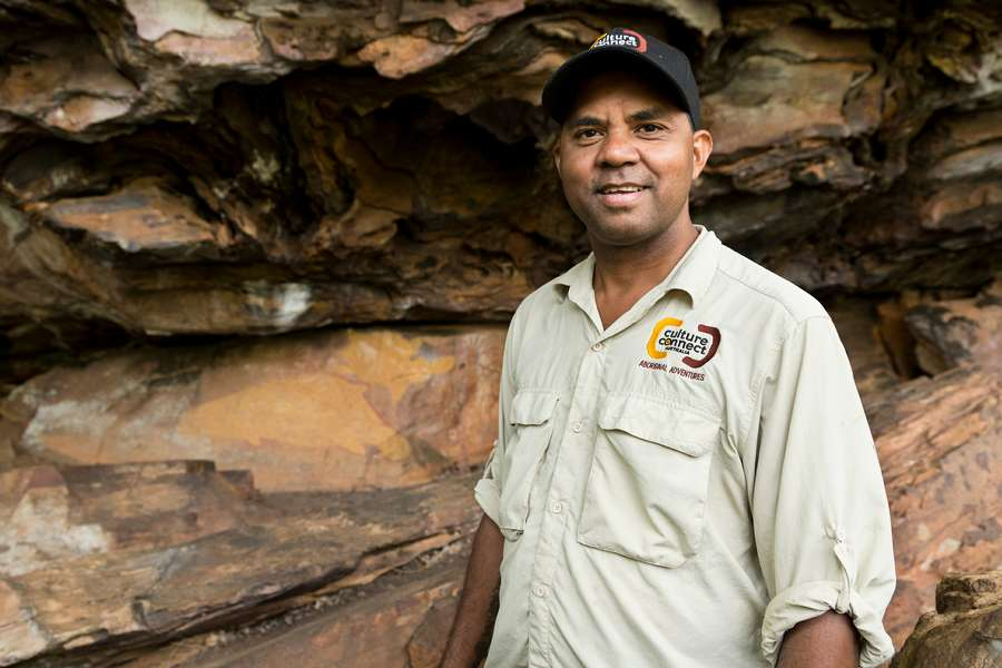 Traditional aboriginal owner of Normanby station standing in front of a rock shelter wearing a culture connect uniform.