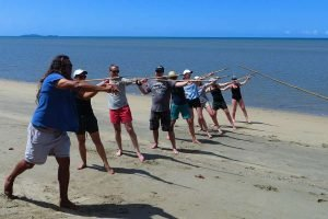 Linc Walker teaching a group of people at Cooya beach how to through a spear, part of the Bama Way