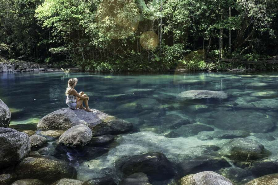 a woman relaxing beside a waterhole in the Daintree National Park