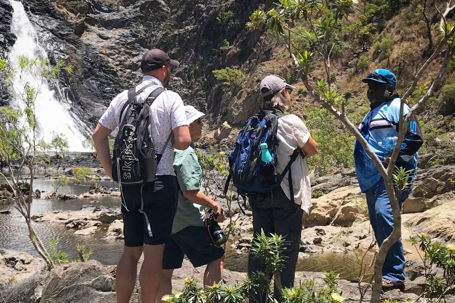A small group of people standing in front of a waterfall learning from a traditional owner of the aboriginal people of the Wujal Wujal