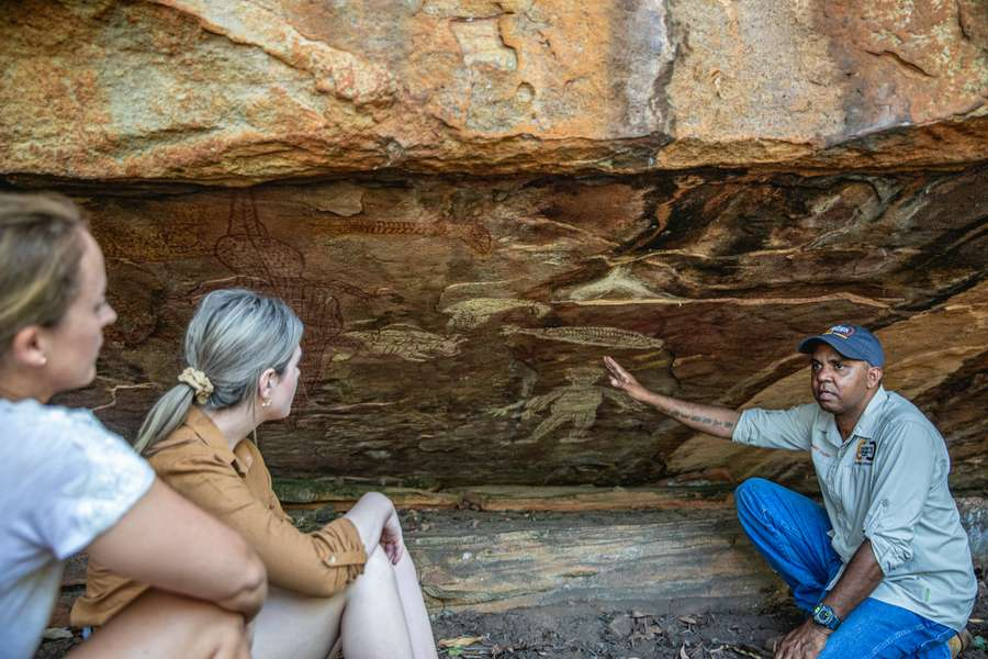 Two people viewing rock art with a traditional owner in Cape York